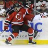 Photo - New Jersey Devils' Adam Henrique (14) checks Columbus Blue Jackets' Nathan Horton during the first period of an NHL hockey game on Thursday, Feb. 27, 2014, in Newark, N.J. (AP Photo/Bill Kostroun)