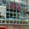 In this Sept. 16, 2012 photo, a cyclist looks back at badly-damaged Japanese supermarket Aeon following an anti-Japan demonstrators\' attack in Qingdao in Sandong Province, China. The craggy island specks in the East China Sea aren\'t even an economic backwater. They have no factories, no highways, no shops, no people — only goats. But the high-pitched row between Beijing and Tokyo over their ownership is exacting a growing toll on Japan, threatening to send its recovery from last year\'s disasters into reverse. (AP Photo/Kyodo News) JAPAN OUT, MANDATORY CREDIT, NO LICENSING IN CHINA, FRANCE, HONG KONG, JAPAN AND SOUTH KOREA