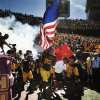 Photo -   Minnesota's Ra'Shede Hageman (99) carries the United States flag as the teamtakes the field to play New Hampshire in an NCAA college football game, Saturday, Sept. 8, 2012, in Minneapolis. Minnesota won 44-7. (AP Photo/Tom Olmscheid)