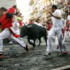 Revelers run in front of a Valdefresno ranch fighting bull during the San Fermin fiestas, Tuesday, July 9, 2013, in Pamplona, Spain. Revelers from around the world come to participate in the street partying festival, which became world famous with the 1926 publication of Ernest Hemingway\'s novel