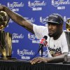 Photo -   Miami Heat small forward LeBron James rests his hand on the Larry O'Brien NBA Championship Trophy during a news conference after Game 5 of the NBA finals basketball series against the Oklahoma City Thunder, Friday, June 22, 2012, in Miami. The Heat won 121-106 to become the 2012 NBA Champions. His most valuable player trophy is at right. (AP Photo/Lynne Sladky)
