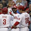Photo - Philadelphia Phillies' Marlon Byrd (3) is cheered by teammates Ryan Howard and Chase Utley (26) after scoring a home run in the first inning of a baseball game against the Washington Nationals, Friday, May 2, 2014, in Philadelphia. (AP Photo/Laurence Kesterson)