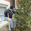 Volunteer Ernie Raper shovels dirt around the roots of a tree as