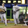 Photo - Pittsburgh Pirates shortstop Jordy Mercer, left, throws to firs for the out after fielding a ground ball by Miami Marlins' Donovan Solano in the fourth inning of a baseball game in Miami, Saturday, June 14, 2014. Josh Harrison (5) backs up the play. (AP Photo/Alan Diaz)