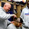 Photo -  In this photo provided by the University of Tulsa Athletic Department, offensive coordinator/offensive line coach Herb Hand, left, cuts the hair of red-shirt freshman offensive tackle Tyler Holmes, center, as Wilson Holloway looks on,  at right,  in an undated photo. Several of Holloway's teammates shaved their heads in solidarity with Holloway, who lost his due to chemotherapy. Holloway, a Tulsa offensive lineman who defeated Hodgkin's lymphoma twice in the past 10 months was honored Thursday Jan. 8, 2009 with the Courage Award from the Football Writers Association of America and the Orange Bowl. (AP Photo/University of Tulsa Athletic Department)