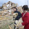Lisa Copeland, right, and Kacie Rose carry a dog to a safe place before a second round of storms approaches Friday, March 2, 2012 in Ooltewah, Tenn. Powerful storms stretching from the Gulf Coast to the Great Lakes flattened buildings in several states, wrecked two Indiana towns and bred anxiety across a wide swath of the country in the second powerful tornado outbreak this week. (AP Photo/Chattanooga Times Free Press, Angela Lewis) MANDATORY CREDIT ORG XMIT: TNCHA104