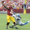 Photo - Washington Redskins quarterback Robert Griffin III is pulled to the turf by Detroit Lions defensive end Willie Young during the first half of a NFL football game in Landover, Md., Sunday, Sept. 22, 2013. (AP Photo/Richard Lipski)