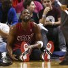 Miami Heat\'s Dwyane Wade (3) tends to his leg after being knocked to the floor during the second half of an NBA basketball game against the Oklahoma City Thunder in Miami, Tuesday, Dec. 25, 2012. The Heat won 103-97. (AP Photo/J Pat Carter) ORG XMIT: FLJC109
