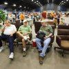 Three men discover chairs displayed for sale are the perfect place to take a break from shopping at a giant