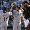 Photo - Milwaukee Brewers' Khris Davis (18) is greeted by teammate Matt Garza (22) after scoring on a single by Lyle Overbay off Pittsburgh Pirates starting pitcher Edinson Volquez during the fourth inning of a baseball game in Pittsburgh Saturday, June 7, 2014. At right is Pirates catcher Russell Martin.(AP Photo/Gene J. Puskar)