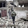 Photo - Free Syrian Army fighters walk amid the ruins of a village situated a short distance from an area where fighting between rebels and government forces continues, Saturday, Dec. 22, 2012. (AP Photo/Virginie Nguyen Hoang)