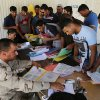 Photo - Iraqi men check in at the main army recruiting center as they volunteer for military services in Baghdad, Iraq, Wednesday, July 9, 2014, after authorities urged Iraqis to help battle insurgents. (AP Photo/Karim Kadim)