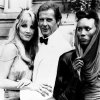 FILE - In this Aug. 17, 1984 file photo, actor Roger Moore, alias British secret agent James Bond, is seen with his co-stars Tanya Roberts, and Grace Jones, right, in front of Chateau de Chantilly, on the set of the 007 action film