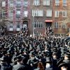 In this March 3, 2013, photo provided by VosIzNeias.com, Orthodox Jewish mourners gather outside the Congregation Yetev Lev D\'Satmar synagogue in Brooklyn\'s Williamsburg neighborhood for the funeral of two expectant parents who were killed in a car accident early Sunday, in New York. The baby of Nachman and Raizy Glauber, a boy, was delivered prematurely by cesarean section and survived until the next morning, but died around 5:30 a.m. on Monday, March 4. Police were searching for the driver of a BMW and a passenger who fled on foot after slamming into the livery cab that was transporting the 21-year-old couple to a hospital. (AP Photo/VosIzNeias.com, Eli Wohl)