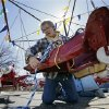 Photo - Hank Gehlhaus prepares the 1930's Kiddie Airplane Ride for opening day at The Keansburg Amusement Park, Saturday, March 23, 2013, in Keansburg, N.J. Founded in 1904, by Gehlhaus' grandfather, the Keansburg Amusement Park, which Superstorm Sandy left under up to six feet of water, opens Saturday even though not all rides will be ready to operate and its popular Wildcat roller coaster is gone. (AP Photo/Mel Evans)