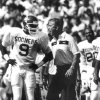OU head college football coach Barry Switzer yells encouragement to his players on the field while defensive back Lonnie Finch gets instructions from the bench. Oct. 10, 1987