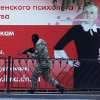 A pro-Russian fighter runs past a huge poster during fighting near a regional police department in downtown Donetsk, eastern Ukraine, Tuesday, July 1, 2014. Ukraine renewed its attacks against armed pro-Russian separatists Tuesday after the president called off a unilateral cease-fire, carrying out air and artillery strikes against rebel positions in eastern Ukraine. (AP Photo/Dmitry Lovetsky)