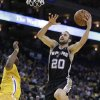 San Antonio Spurs\' Manu Ginobli (20) goes to the basket next to Golden State Warriors\' Carl Landry during the first half of an NBA basketball game Friday, Feb. 22, 2013, in Oakland, Calif. (AP Photo/Ben Margot)