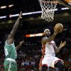 Photo - Miami Heat's LeBron James, right, shoots as Boston Celtics' Brandon Bass, left, defends during the first half of an NBA basketball game Saturday, Nov. 9, 2013, in Miami. (AP Photo/Lynne Sladky)