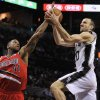 San Antonio Spurs guard Manu Ginobili, right, of Argentina, shoots against Portland Trailblazers forward Thomas Robinson during the first half of an NBA basketball game on Wednesday, March 12, 2014, in San Antonio. (AP Photo/Darren Abate)