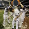 Photo - Milwaukee Brewers' Yovani Gallardo is dunked by teammates Mark Reynolds (7) and Carlos Gomez after hitting a game-winning double during the 10th inning of a baseball game against the Baltimore Orioles Tuesday, May 27, 2014, in Milwaukee. The Brewers won 7-6. (AP Photo/Morry Gash)