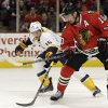 Photo - Chicago Blackhawks' Patrick Sharp (10) controls the puck against Nashville Predators' Craig Smith (15) during the first period of an NHL hockey game in Chicago, Friday, March 14, 2014. (AP Photo/Nam Y. Huh)