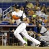 Photo - Miami Marlins' Giancarlo Stanton, left, watches after hitting an RBI-single to score Marcell Ozuna during the first inning of an interleague baseball game against the Seattle Mariners, Friday, April 18, 2014, in Miami. Mariners catcher Mike Zunino, right, looks on. (AP Photo/Lynne Sladky)