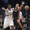 Photo - Brooklyn Nets guard Joe Johnson (7) passes the ball against Miami Heat forward Shane Battier in the second period during Game 3 of an Eastern Conference semifinal NBA playoff basketball game on Saturday, May 10, 2014, in New York. (AP Photo/Julie Jacobson)