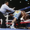 Photo - Marcos Maidana, center, from Argentina, knocks Floyd Mayweather Jr. through the ropes in their WBC-WBA welterweight title boxing fight Saturday, May 3, 2014, in Las Vegas. At left is referee Tony Weeks. (AP Photo/Eric Jamison)