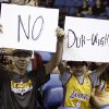 Los Angeles Lakers fans 12-year-old Ian Klock and his 9-year-old brother Nate Klock, both from Upland, Calif., display posters about Dwight Howard, prior to the Lakers\' NBA basketball preseason game against the Golden State Warriors on Saturday, Oct. 5, 2013, in Ontario, Calif. (AP Photo/Alex Gallardo)