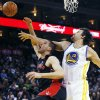 Toronto Raptors\' Jonas Valanciunas, left, shoots as Golden State Warriors\' Andrew Bogut defends during the first half of an NBA basketball game in Oakland, Calif., Monday, March 4, 2013. (AP Photo/George Nikitin)