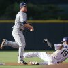 San Diego Padres second baseman Jedd Gyorko, left, throws to first base after forcing out Colorado Rockies\' Charlie Blackmon at second base on the front end of a double play hit into by Drew Stubbs in the first inning of a baseball game in Denver on Saturday, May 17, 2014. (AP Photo/David Zalubowski)