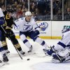 Photo - Boston Bruins left wing Daniel Paille (20) shoots and scores past Tampa Bay Lightning goalie Anders Lindback as defenseman Keith Aulie (3) watches during the second period of an NHL hockey game in Boston Monday, Nov. 11, 2013. (AP Photo/Elise Amendola)
