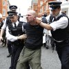 Photo -   British police officers arrest a protesters in support of WikiLeaks founder Julian Assange from the front of Ecuadorian Embassy in central London, London, Thursday, Aug. 16, 2012. WikiLeaks founder Julian Assange entered the embassy in June in an attempt to gain political asylum to prevent him from being extradited to Sweden, where he faces allegations of sex crimes, which he denies. (AP Photo/Sang Tan)