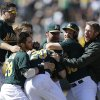 Photo - Oakland Athletics' Josh Donaldson (20) is mobbed by teammates after hitting the game-winning single in the 11th inning of a baseball game against the Boston Red Sox on Sunday, July 14, 2013, in Oakland, Calif. The A's won 3-2. (AP Photo/Ben Margot)