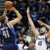 Photo - Dallas Mavericks' Dirk Nowitzki, left, of Germany, shoots as Minnesota Timberwolves' Kevin Love defends in the first quarter of an NBA basketball game, Monday, Dec. 30, 2013, in Minneapolis. (AP Photo/Jim Mone)