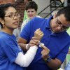 Martin Orozco places a participant\'s armband on the wrist of Gabriela Salazar during the 2012 Oklahoma City Walk to End Alzheimer\'s at Bricktown Ballpark in Oklahoma City, OK, Saturday, September 15, 2012, By Paul Hellstern, The Oklahoman