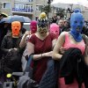 Five women wearing balaclavas, two of whom are members of the Russian punk group Pussy Riot, make their way through a crowd after they were released from a police station, Tuesday, Feb. 18, 2014, in Adler, Russia. No charges were filed against the Pussy Riot members Nadezhda Tolokonnikova, in the blue balaclava, and Maria Alekhina, in the pink, who were held along with several other people near the city\'s ferry terminal. (AP Photo/Morry Gash)