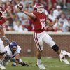 OU: University of Oklahoma quarterback Sam Bradford throws on the run against TCU in the first quarter of an NCAA college football game in Norman, Okla., Saturday, Sept. 27, 2008. Oklahoma outside linebacker Jon Cooper and TCU linebacker Jason Phillips are at left. (AP Photo/Sue Ogrocki) ORG XMIT: OKSO104