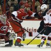 Carolina Hurricanes goalie Dan Ellis (31) and teammate Jay Harrison (44) defend against New Jersey Devils\' Adam Henrique (14) during the second period of an NHL hockey game in Raleigh, N.C., Thursday, March 21, 2013. Henrique scored on the play. (AP Photo/Gerry Broome)
