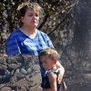 Tracy Streeper comforts five year-old grandson Jesse, as they stand on the north side of Streeper\'s destroyed home. The Streepers had lived in this house for one year. Residents in Luther were allowed to return to the their homes early Saturday, Aug. 4, 2012, after they fled a rapidly moving wildfire yesterday that consumed at least seven structures on South Dogwood Street, leaving smoldering ashes where family homes once stood. Photo by Jim Beckel, The Oklahoman.