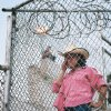 Crystal Herrington stands behind a fence looking at her son on the other side at the 2007 Oklahoma Prison Rodeo. photo provided