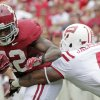 Photo -   Alabama running back Eddie Lacy (42) runs through the tackle of Western Kentucky linebacker Andrew Jackson (4) in the first half of an NCAA college football game at Bryant Denny Stadium in Tuscaloosa, Ala., Saturday, Sept. 8, 2012. (AP Photo/Dave Martin)