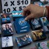 A woman picks up a magnet for sale that reads in Spanish