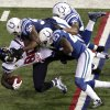 Photo - Houston Texans' Andre Johnson (80) is tackled by Indianapolis Colts' Jerrell Freeman (50), Vontae Davis (23) and Joe Lefeged (35) during the second half of an NFL football game, Sunday, Dec. 30, 2012, in Indianapolis. (AP Photo/AJ Mast)