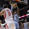 Photo - Memphis Grizzlies forward James Johnson (3) dunks in front of Houston Rockets' Omri Casspi (18) during the first half of an NBA basketball game Thursday, Dec. 26, 2013, in Houston. (AP Photo/Bob Levey)