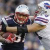 Photo - FILE - In this Jan. 1, 2012 file photo, New England Patriots tight end Aaron Hernandez (81) tries to break free of Buffalo Bills linebacker Chris Kelsay (90) during the fourth quarter of an NFL football game in Foxborough, Mass. Hernandez has been taken from his home in handcuffs, Wednesday, June 26, 2013, after a Boston semi-pro football player was found dead in an industrial park a mile from his house.  (AP Photo/Elise Amendola, File)