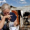 Susan Harmon is unable to contain her emotions and she sobs after finding a scorched photo album in the rubble of her home Tuesday afternoon, July 19, 2011. Pal, the family\'s pet mutt, awakened Susan Harmon with constant barking Sunday night when the home caught fire. Susan\'s son, Walt, credits the pet with saving his life and allowing him to rescue his mother, and her parents, Donald and Donna Gilliam. from the smoke-filled home before it was destroyed by flames. The home is in rural Lincoln County about six miles north of Jacktown. Photo by Jim Beckel, The Oklahoman