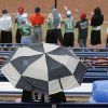 A softball fan braves the rain under an umbrella to watch the Class 4A Oklahoma State High School Slow Pitch Softball Championship at ASA Hall of Fame Stadium in Oklahoma City, Wednesday, May 1, 2013. Photo by Chris Landsberger, The Oklahoman