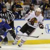 Chicago Blackhawks\' Marian Hossa (81), of Sweden, and St. Louis Blues\' Jay Bouwmeester (19) reach for a loose puck during the first period in Game 2 of a first-round NHL hockey playoff series on Saturday, April 19, 2014, in St. Louis. (AP Photo/Bill Boyce)